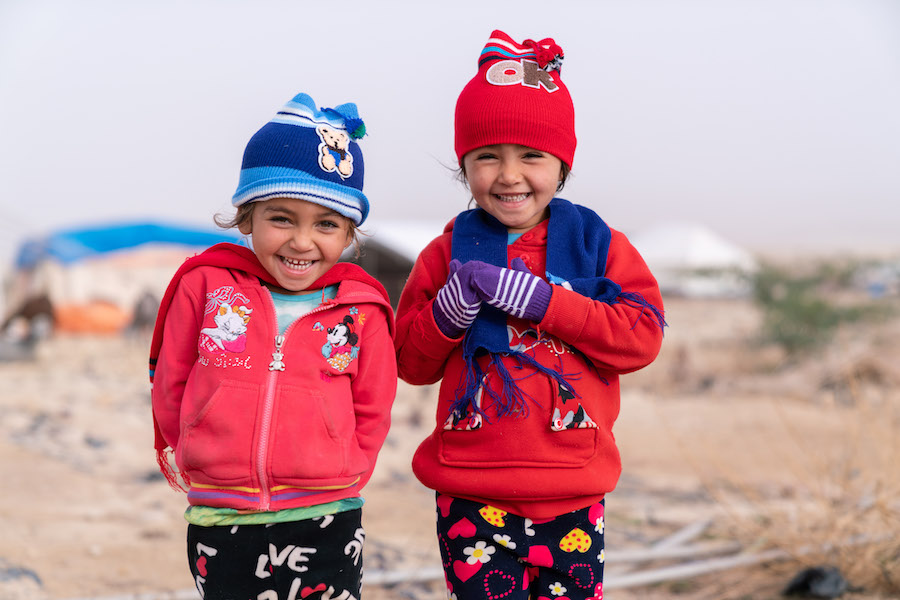 Sita, 4 years, and Tawaseef, 5 years, wearing their new winter clothes. Their family are Syrian refugees and both girls were born in Jordan. They have just received their winter clothing kits from UNICEF and its partner Mateen.