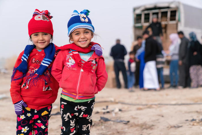 Young Syrian refugees living in Jordan wearing warm winter clothing provided by UNICEF.