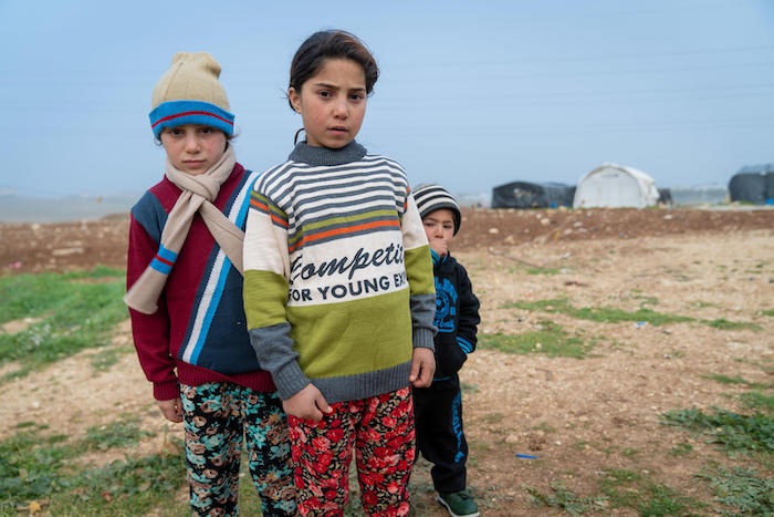 From left: Syrian refugees Yasmeen, 8, Zainab, 9, and Mohammad, 3, wear warm winter clothes they received from UNICEF and partner Mateen in Jordan.