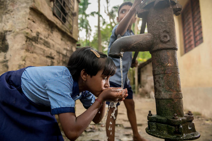 A girl drinks from a hand pump installed by UNICEF and partners in Gondharbapur village, West Bengal, India.