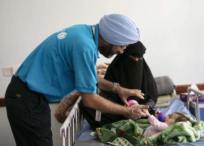 UNICEF Nutrition Manager Karanveer Singh cares for a malnourished child in Sana'a, Yemen in October 2018.