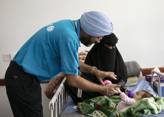 Karanveer Singh, UNICEF Yemen Nutrition Manager, cares for a severely malnourished baby in Sana'a, Yemen in October 2018.