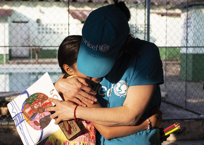A UNICEF volunteer hugs a 10-year-old girl whose mother was killed by gang violence in Honduras.