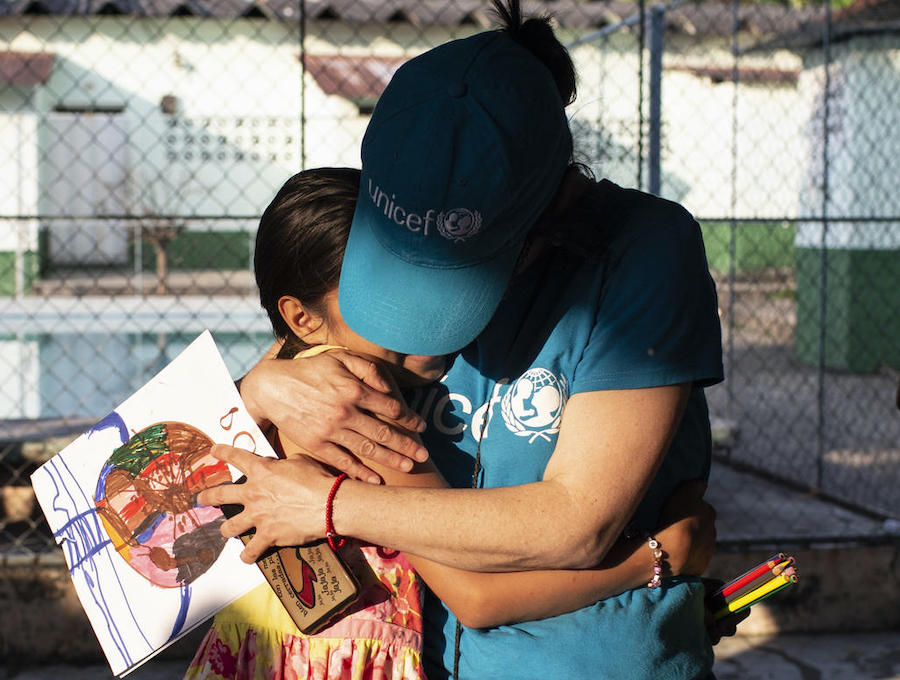 Jennifer, 10, who fled Honduras with her three siblings after their mother was killed by a gang, hugs a UNICEF volunteer at a hotel for asylum seekers in Tapachula, Mexico.