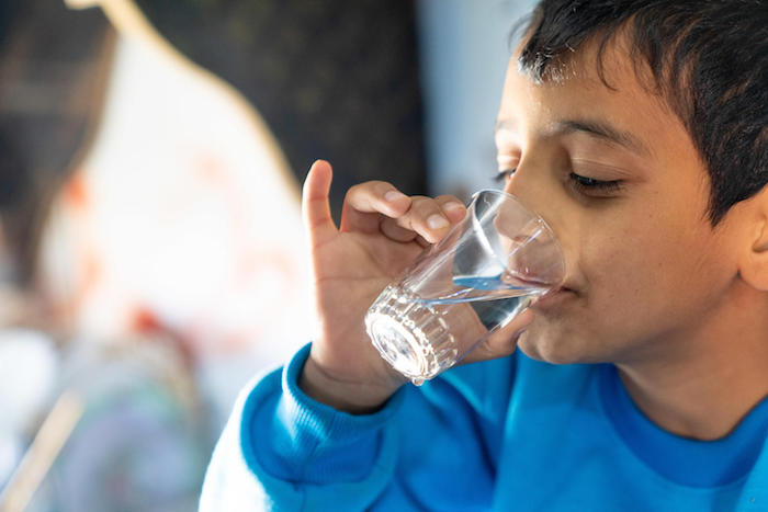 Syrian refugee Diaa, 10, drinks water from a tap installed by UNICEF and partners in Za'atari Refugee Camp, Jordan.