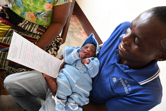 A father holds his newborn baby daughter and her newly issued birth certificate at the UNICEF-supported hospital in Sibiti, in the south of Congo, on February 20, 2019.