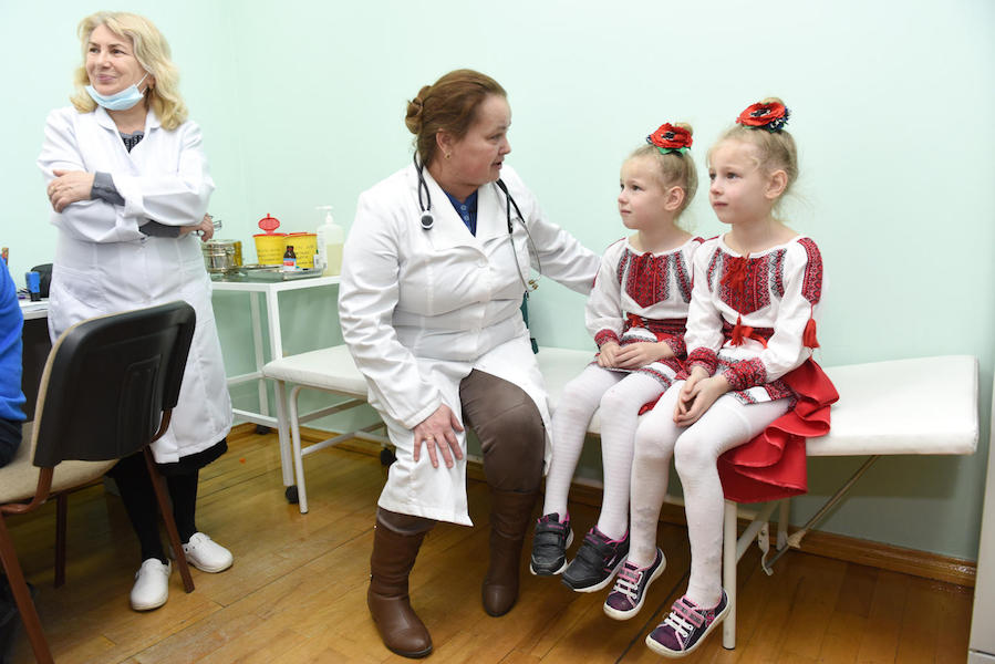 A UNICEF-supported health worker comforts 6-year-old sisters Vitalina and Yuliana before their measles, mumps and rubella vaccination in February 2019 in the Lapaivka village school in western Ukraine's Lviv region.