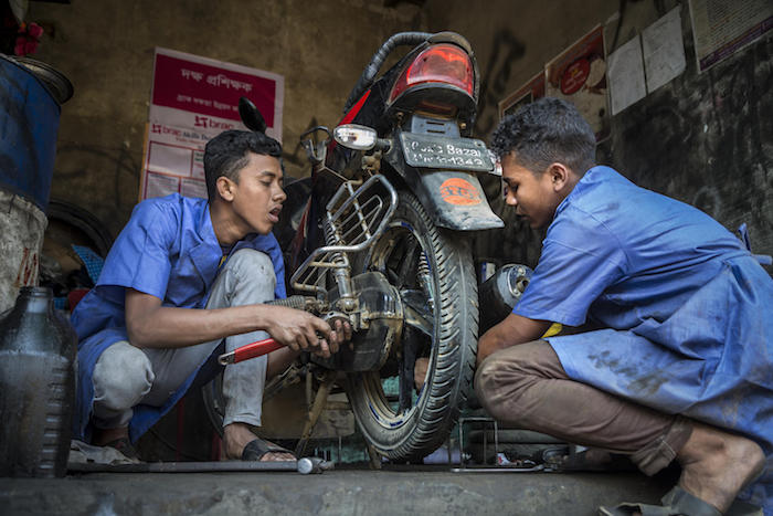 In February 2019 in Bangladesh, 18-year-olds Mohammed (left) and Biplob work on a motorbike as part of a UNICEF-supported vocational training program in Court Bazar, in the Cox's Bazar district.