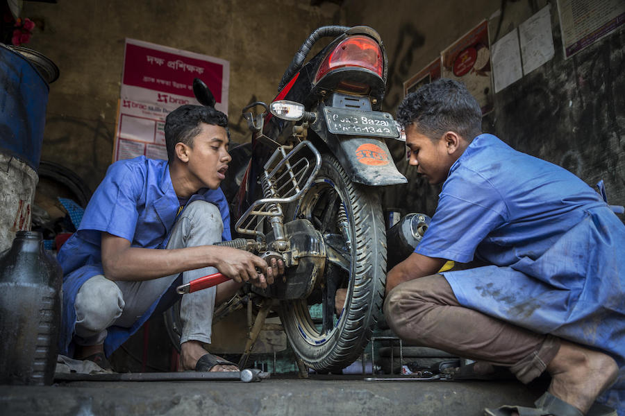Mohammed (left) and Biplob, both 18, work on a motorbike in a UNICEF-supported job skills training program in Court Bazar in the Cox's Bazar district of Bangladesh in February 2019.