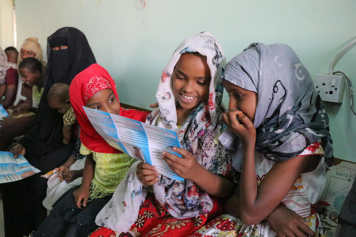 Girls in Aden, Yemen read through brochures while they wait to be vaccinated during a UNICEF-backed immunization campaign in February 2019.