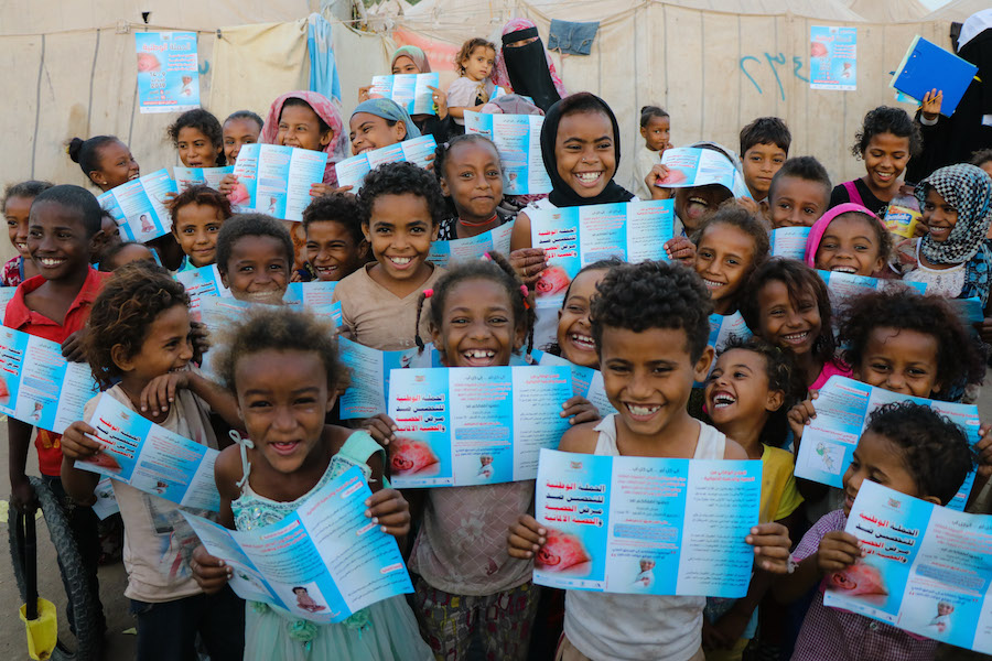 Kids in Aden, Yemen, hold up a UNICEF provided brochure that explains the safety and efficacy of the measles and rubella vaccine kids need to stay healthy.