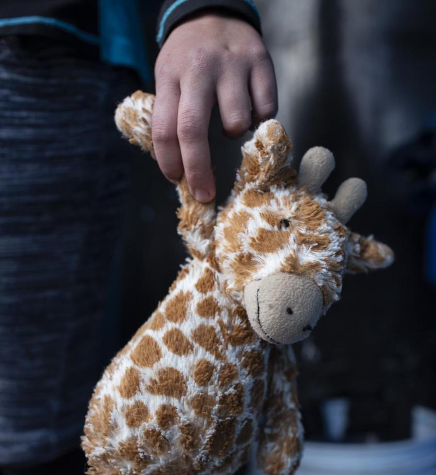 At a shelter for unaccompanied migrant adolescents in Tijuana, Mexico in February 2019, Maylin, 15, holds the toy giraffe she carries with her on the caravan.