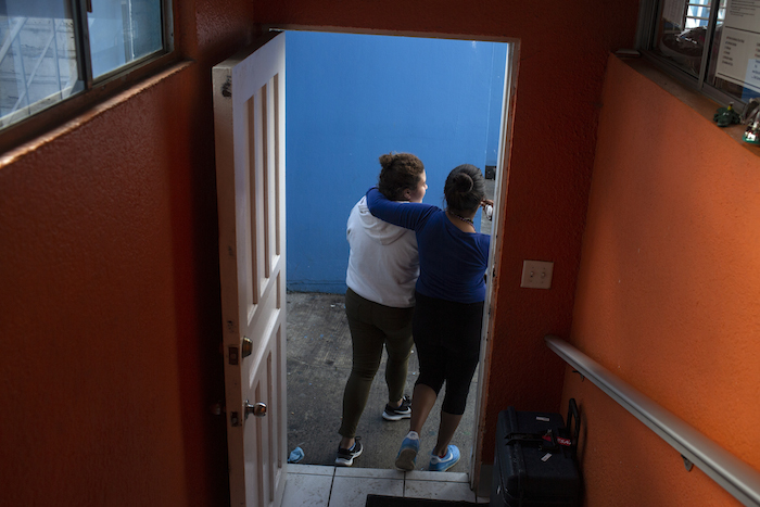 Two teens from Central America walk out of an open-door shelter for unaccompanied migrant adolescents in Mexico.