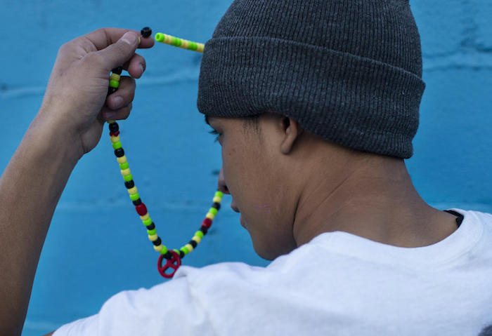 A 17-year-old from Guatemala staying at a shelter for unaccompanied migrant adolescents in Tijuana, Mexico holds the necklace his mother gave him for good luck on his journey north.