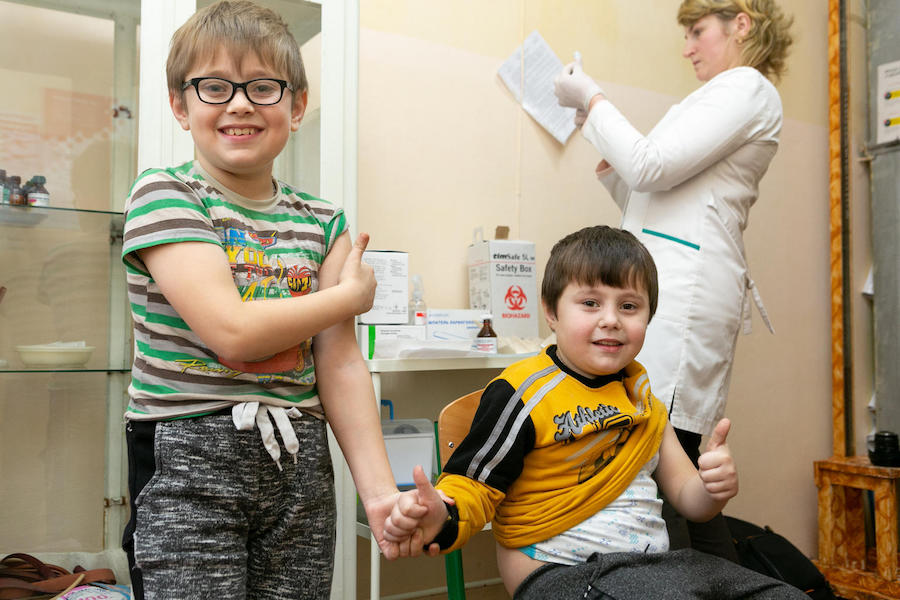 Liubomyr, 8, and his brother Bohdan, 6, held hands while Bohdan received his measles, mumps and rubella vaccination in western Ukraine's Lviv region in February 2019.