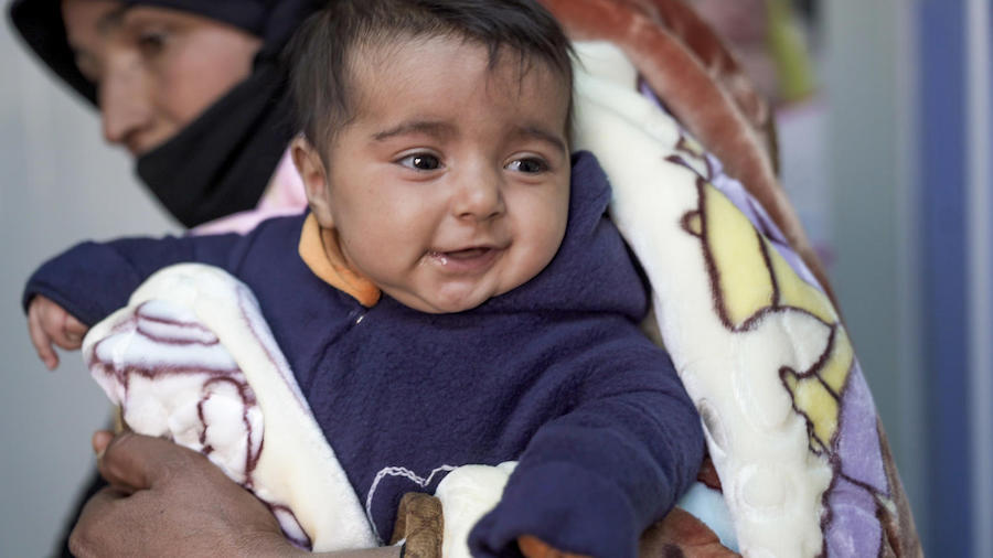 In Jordan, 3-month-old Hala wears a fleece jumpsuit sewn by Syrian refugees in a UNICEF-backed sewing workshop in Za'atari Refugee Camp.