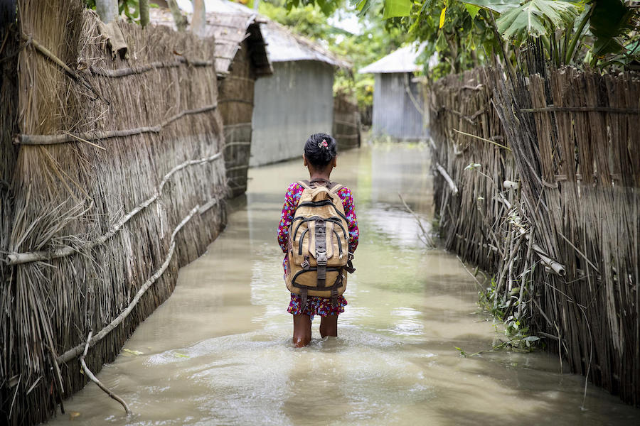 A child wades through water on her way to school in Kurigram district in northern Bangladesh during floods in August 2016.