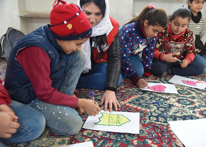 Bajan, 10, (in red hat) draws with friends at a UNICEF-supported primary school in Aleppo, Syria in 2019.