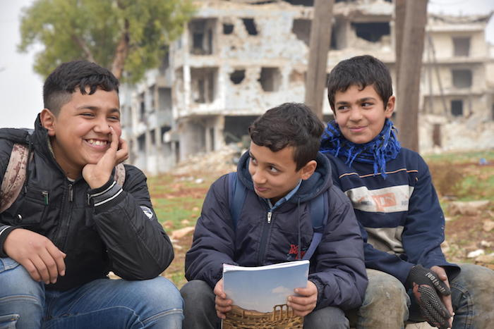 In Aleppo, Syria in 2019, Hussein and Mohammed are in school. Their friend Mustafa, 12, (right) dropped out to help support his family.