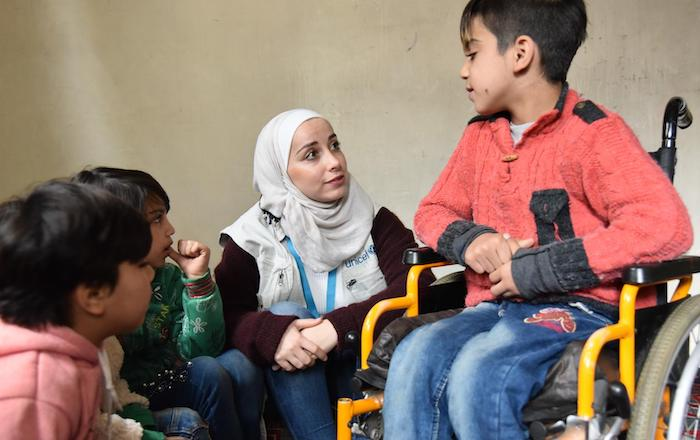 In Aleppo, Syria, a UNICEF staffer talks with 11-year-old Abdullah, who was injured in a bomb blast that killed his father and brother.
