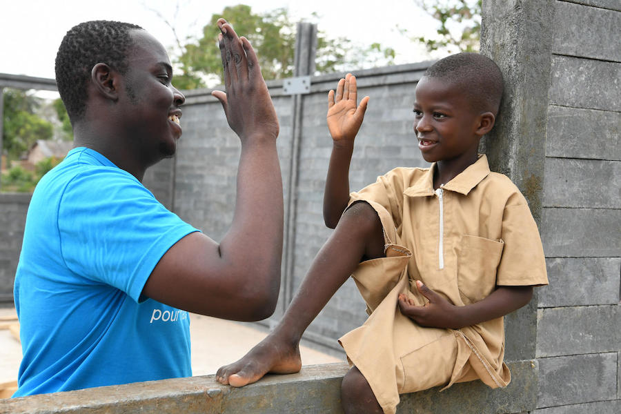 In February 2019, UNICEF staff member Stéphane Gbonikan and a student high five on the site of a new classroom built of recycled plastic bricks in Sakassou, Côte d'Ivoire.