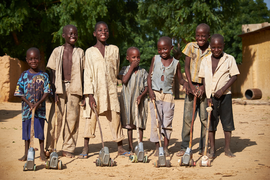 Boys stand with homemade toys in the village of Kadazaki, Matameye department, Niger on August 14, 2016.