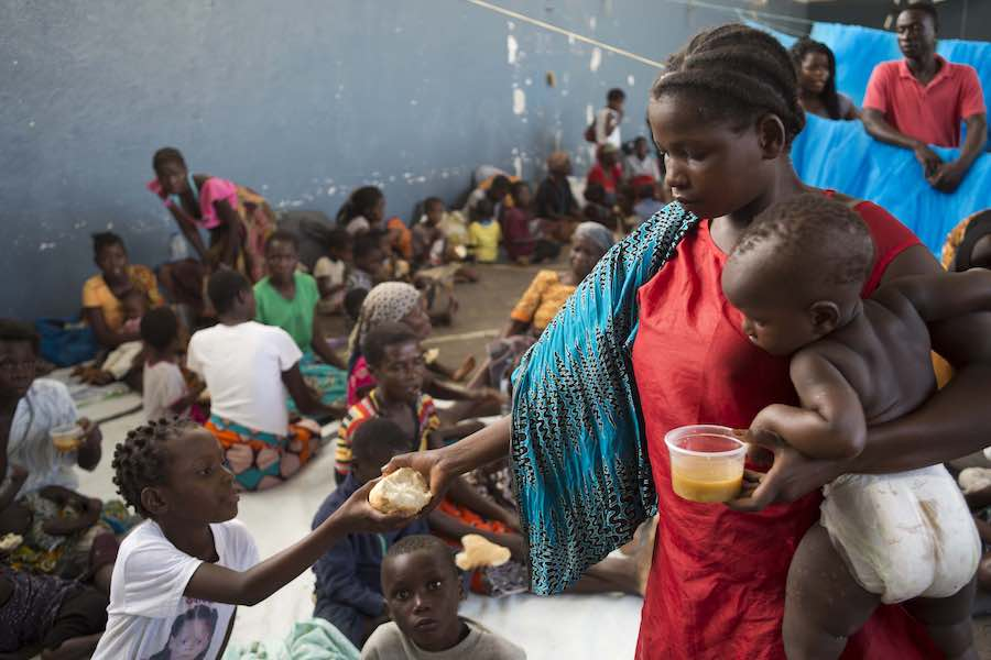Children receive food from a supermarket chain at the Samora Machel school where they were brought after their homes were destroyed and flooded in Buzi, Mozambique, on Saturday 23 March 2019.