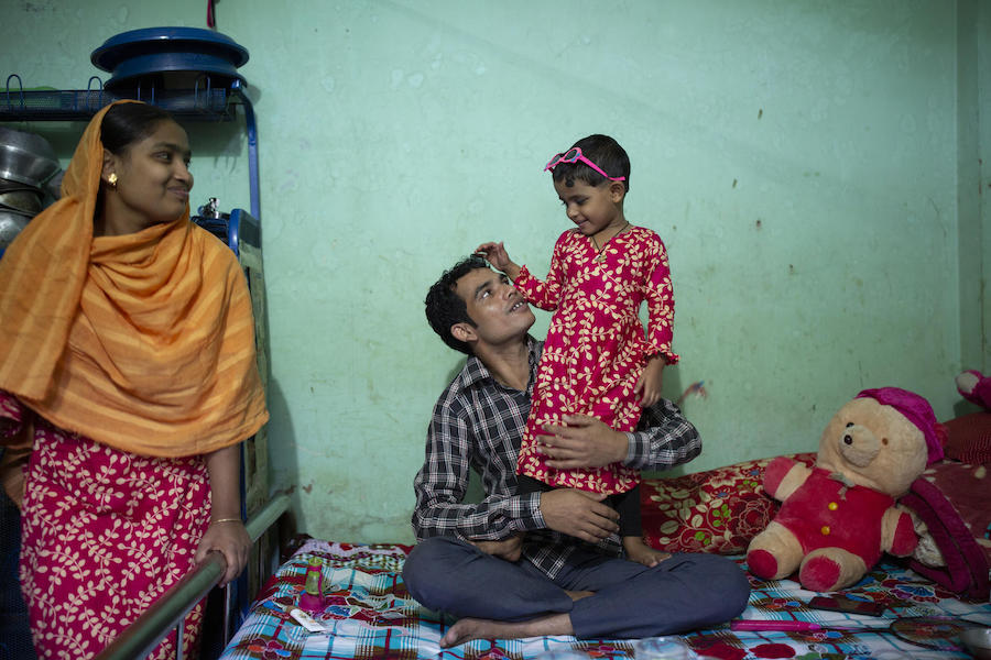 Shumi Akhter, 20, the wife of Jamal Hossain, 26, looks on while he plays with his daughter, Jui, 30 months, at their home near the Northern Tosrifa Group garment factory where they work in Gazipur, outside Dhaka, Bangladesh on December 5, 2018.
