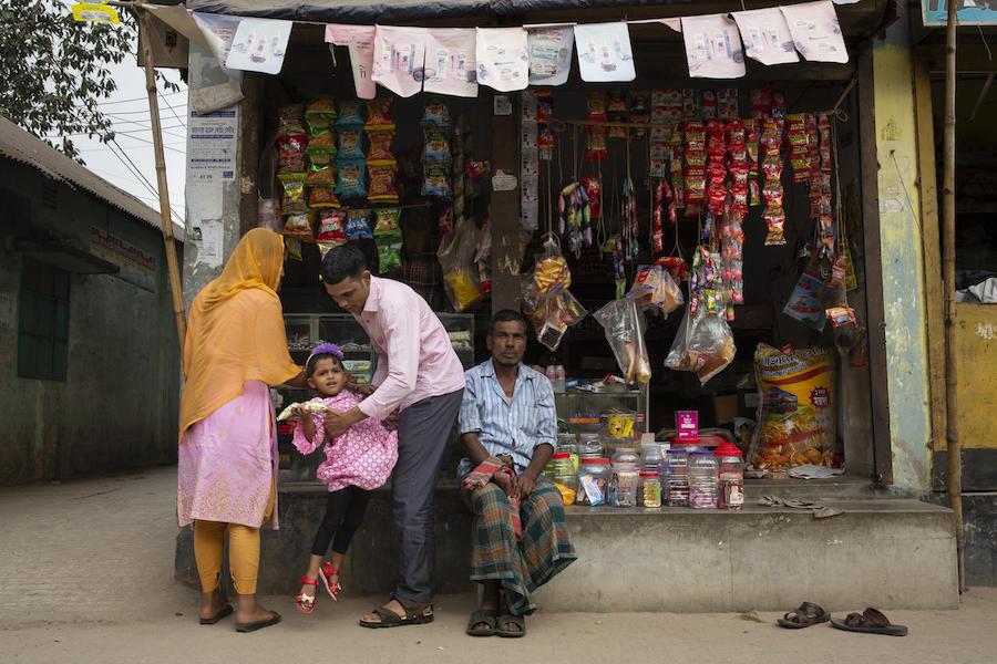 Jamal Hossain, 26, his wife, Shumi Akhter, 20, and their 2 1/2-year-old daugher, Jui, shop for treats near their home in Gazipur outside Dhaka, Bangladesh on December 6, 2018.