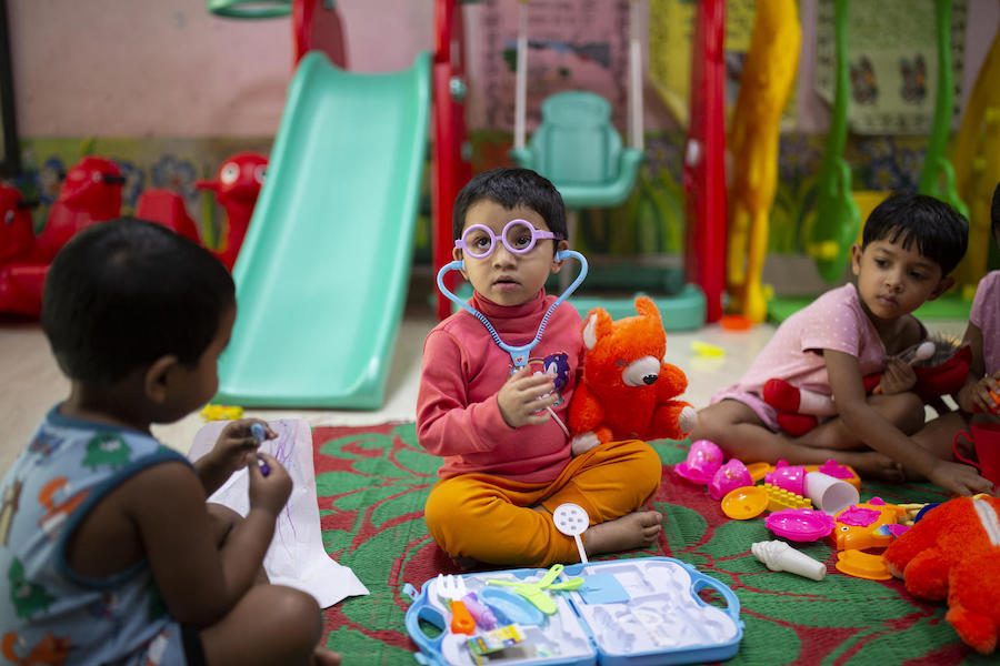 Jisha, 3, years play with a toy stethoscope and medical kit at at the Early Childhood Development (ECD) day care centre located on the Fakir Fashion Ltd. factory where both her parents work in Narayangonj, outside Dhaka, Bangladesh on December 10, 2018.