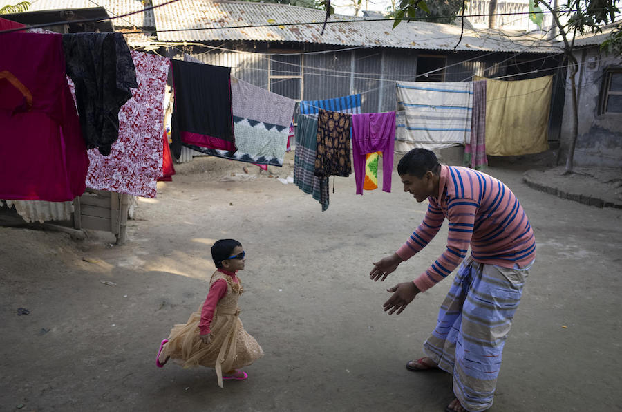 After he comes home from work, Mohammad Jahirul Islam, 28, plays with his daughter, Jisha, 3, in the courtyard outside their home in Narayangonj, outside Dhaka, Bangladesh on December 10, 2018