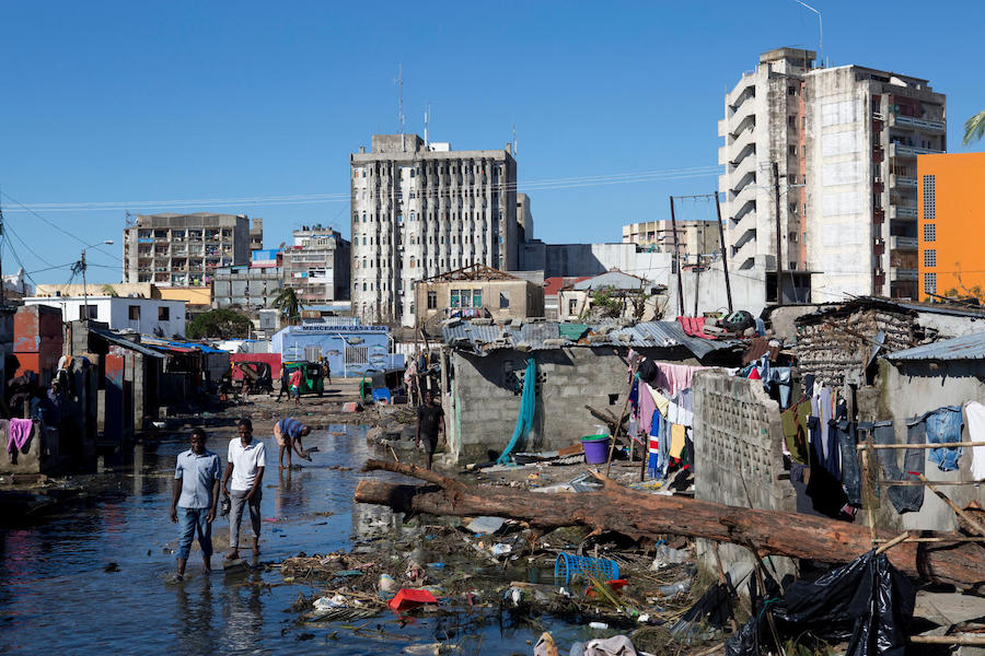On March 24, 2019 in Beira, Mozambique, people walk in an area that was flooded after Cyclone Idai made landfall.