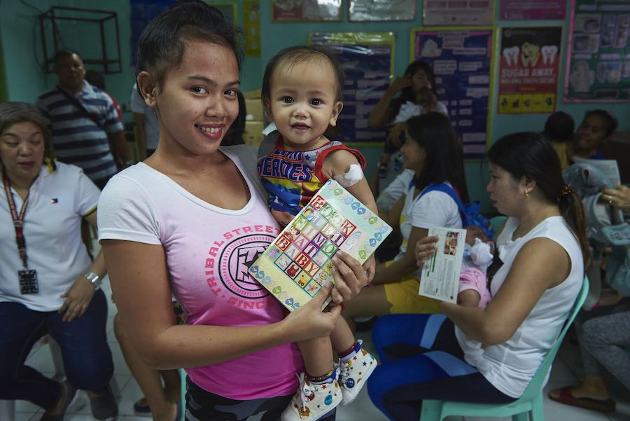 Bernadette Servano's baby Jhay Clifford just received a vaccination that protects against measles, mumps and rubella (MMR) at a health center in Taguig City, the Philippines. © UNICEF/UN0296790/Noorani © UNICEF/UN0296790/Noorani