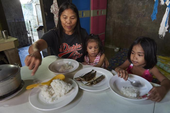 Shirly Mendez feeds her youngest daughter Anika and her granddaughter (right) in her house in Taguig City, the Philippines.