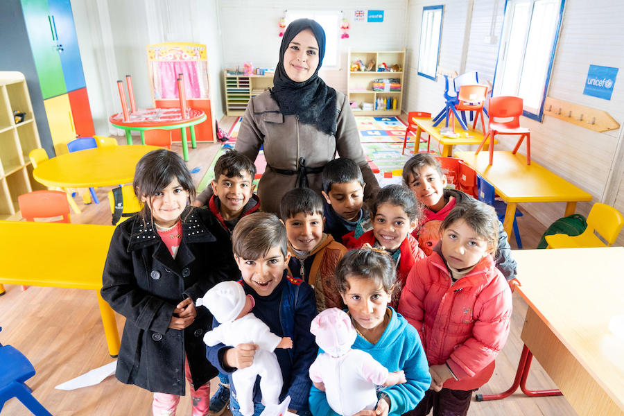 Syrian refugee children and their teacher in a UNICEF-built and -equipped kindergarten in Jordan's Za'atari Refugee Camp in March 2019.