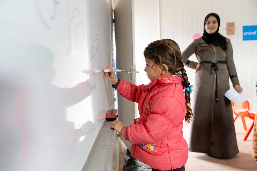 Maya, 6, practices writing letters and numbers in her new kindergarten classroom, built and equipped by UNICEF at Za'atari Refugee Camp in Jordan in 2019.