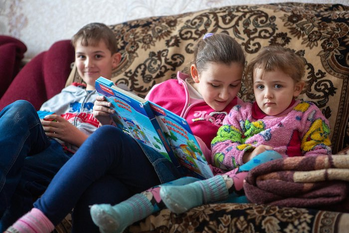 Sergiy,11, Tanya, 10 and Anna, 4 reading a book at their home in Pokrovsk. The family with five children has been suffering hardship, since the conflict began. © UNICEF/UN0300591/Filippov