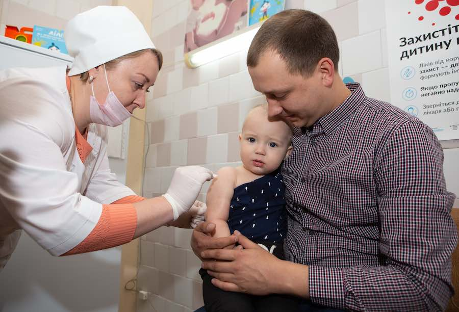 David Bielik, 1.2 y.o., is held by his father Bohdan, as he receives his first dose of MMR vaccine from measles, mumps and rubella from nurse Svitlana Ostapysko in a state polyclinic of Shevchenkivsky district in the centre of Kyiv, Ukraine, on Tuesday, 1