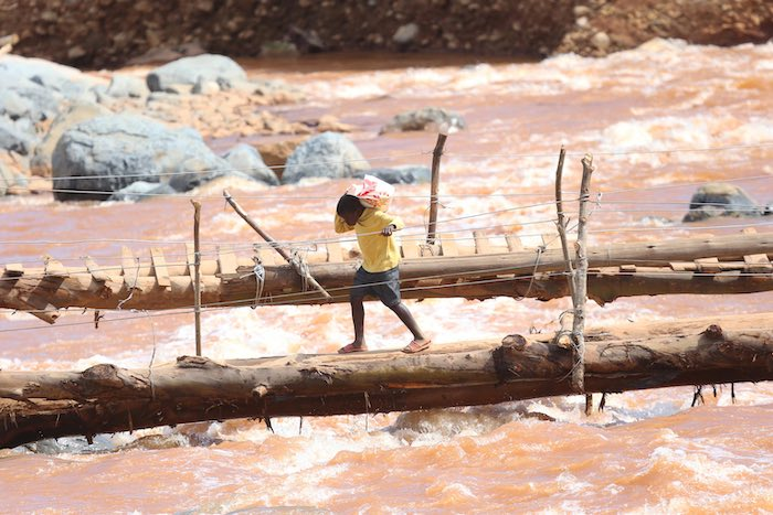 A young boy crosses a bridge near a spot where houses were swept away when Cyclone Idai hit Coppa in Risitu Valley Chimanimani in this Wednesday, April, 10, 2019 photo.The two boys both lost their parents when the cyclone struck the valley. Gore still rem