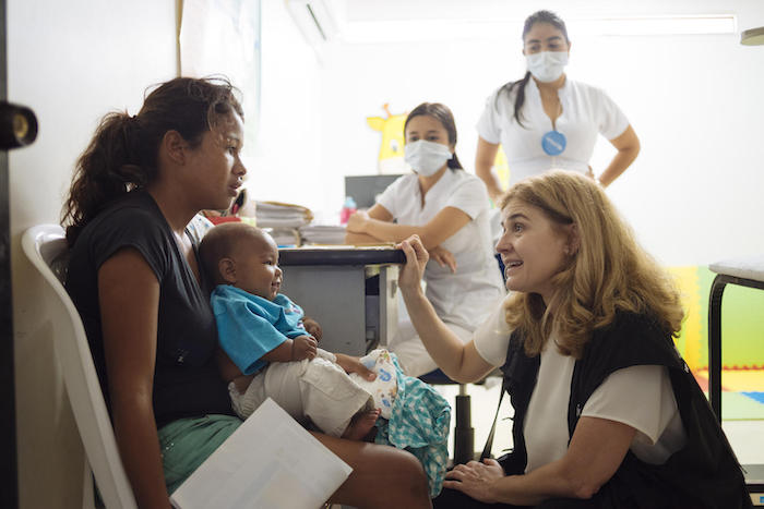 On April 23, 2019 in Cucuta, Colombia, UNICEF Director of the Division of Communication Paloma Escudero speaks with a woman and her child at the UNICEF-supported health center.