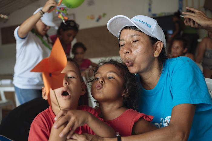 On April 25, 2019, volunteer Pureza Peña, right, plays with children from Venezuela as part of a UNICEF-supported program for migrant families in Colombia.