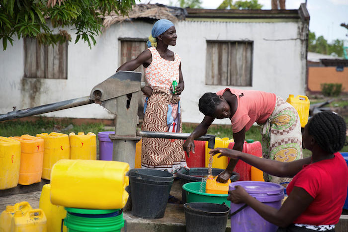 A woman puts drops of disinfectant into water to prevent cholera at a community water point in Dondo, Mozambique on April 14, 2019.