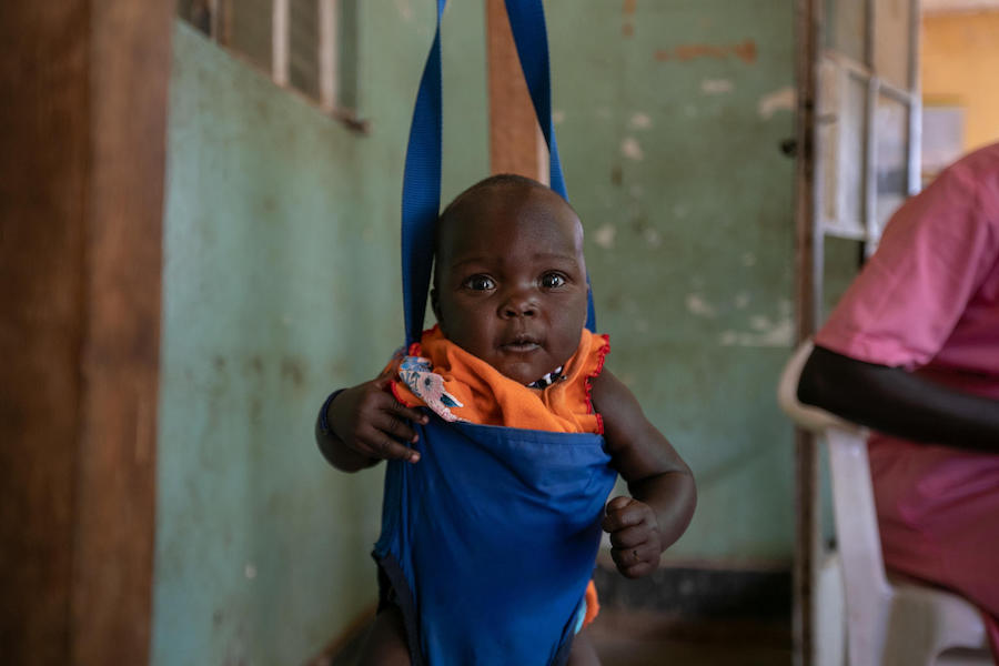 A baby is weighed before immunization at the UNICEF-supported Karenga HC IV in northern Uganda's Kaabong District on April 4, 2019.