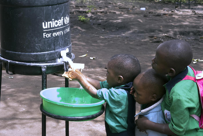 In 2019, pupils at Nyabugando Parents Primary School near the Uganda-DRC border wash as part of the response to the Ebola outbreak, supported by UNICEF and other aid agencies including WHO and the Ugandan government.