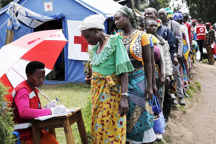 A Uganda Red Cross volunteer registers a woman as people from Democratic Republic of Congo line up at a UNICEF-supported screening facility at a point of entry at Uganda-DRC border town of Bunagana in Kisoro district in 2019.
