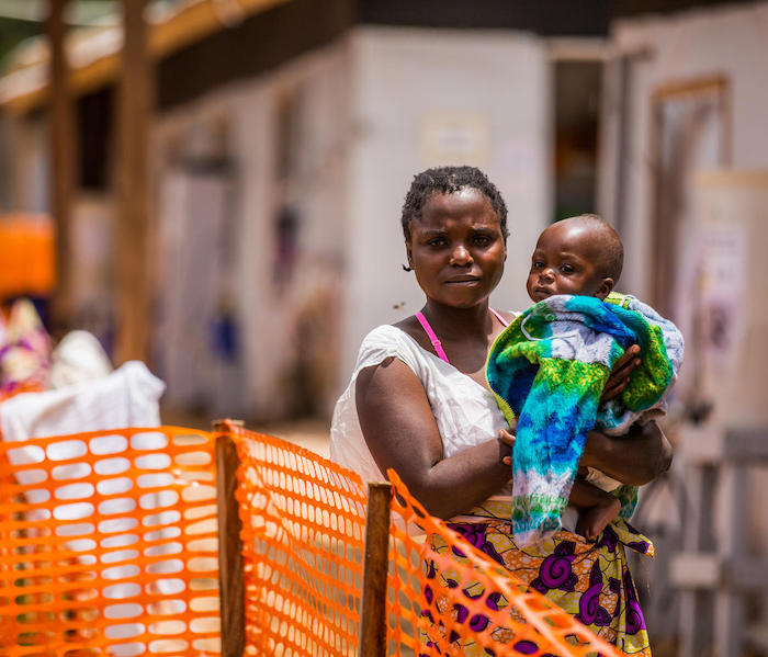 Masika Mbweki, 31, holds her son, Japhet, 10 months, by their room in the quarantine area of the Ebola Teatment Centre of Butembo, Democratic Republic of Congo, 22 March 2019.