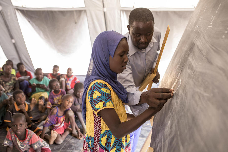 Boureima Tall teaches arithmetic to displaced students in a tent provided by UNICEF in Socoura IDP camp in Sévaré, Mopti region, Mali in April 2019.