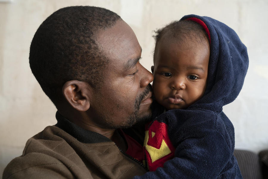 Congolese refugee Dieu-Merci Matala, 44 holds his 7-month-old daughter, Grace, at their apartment in Maitland, Cape Town, South Africa in May 2019.