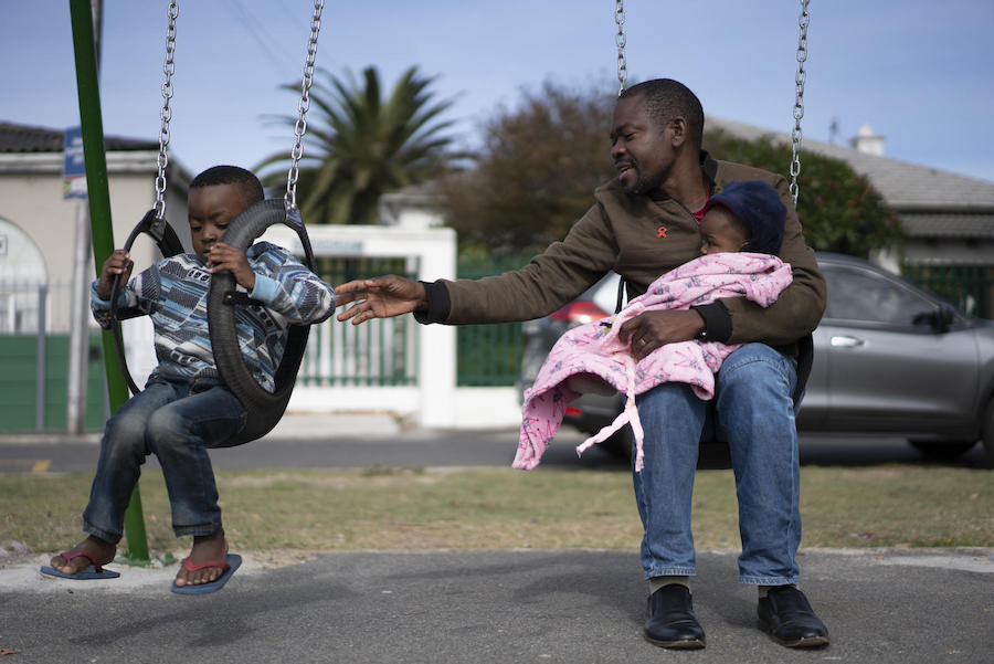 Dieu-Merci Matala, 44, holds his 7-month-old daughter, Grace, while pushing his 4-year-old son, Joshua on the swing in Maitland, Cape Town, South Africa in May 2019.