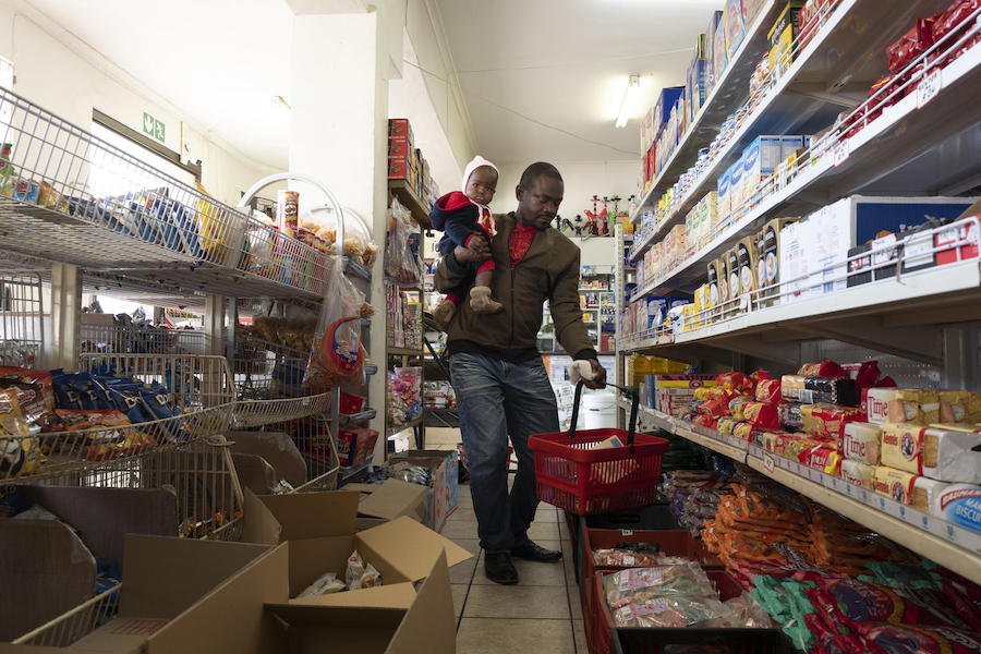 Dieu-Merci Matala, holds his 7-month-old daughter as he shops for groceries for his family in Maitland, Cape Town, South Africa in May 2019.